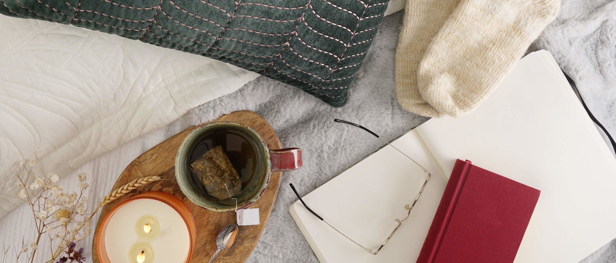 Close-up view of cozy cup of tea next to a lit candle, open notebook, and socks.