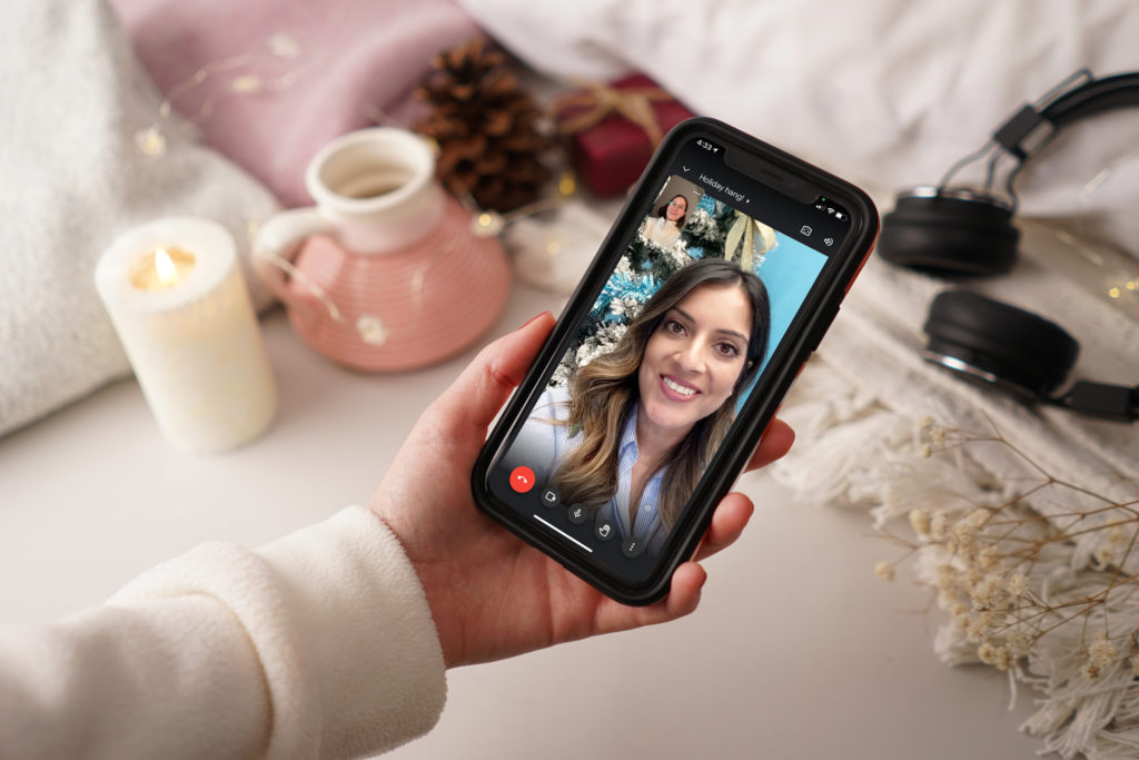 Hand holding phone, screen showing two women having a video call.