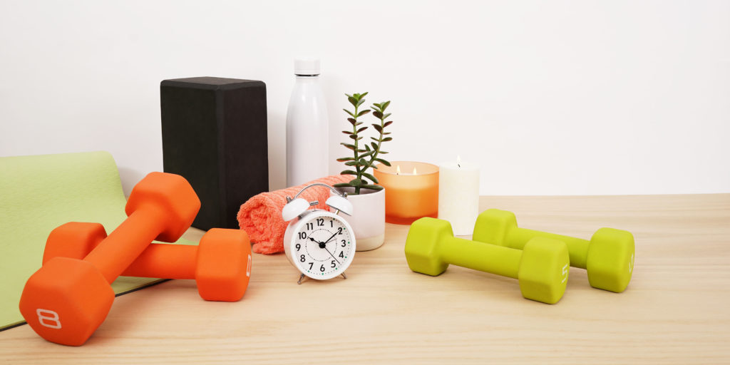 yoga mat, weights, yoga block, candles, rolled up towel
