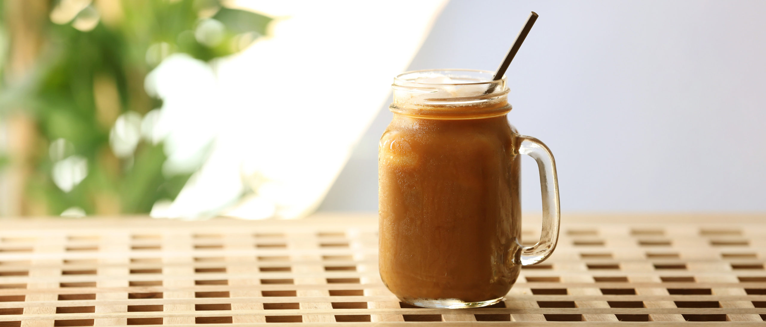 Iced coffee in a mason jar with a straw on a wooden surface.