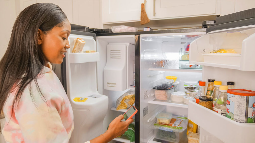 Smiling woman in front of her open fridge, looking at her phone.