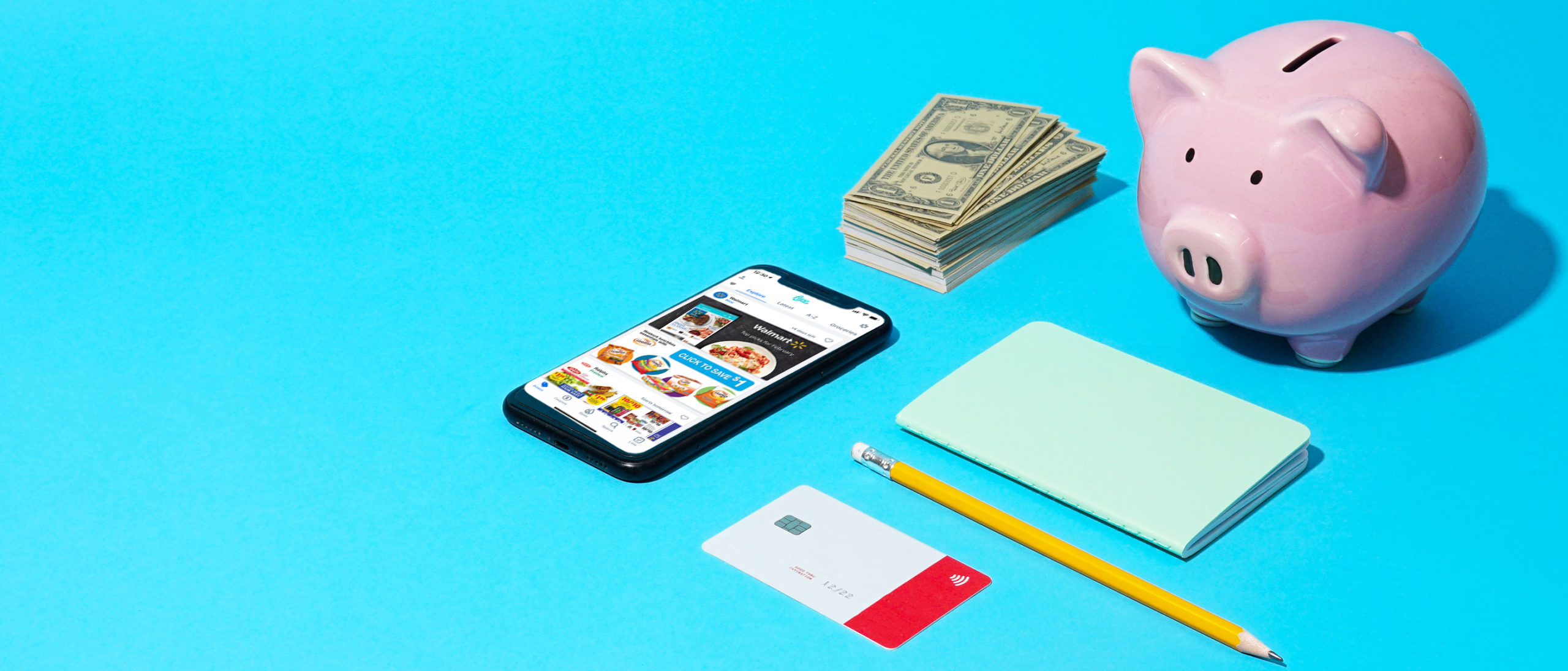 A phone, stack of cash, piggy bank, and notepad on a blue background