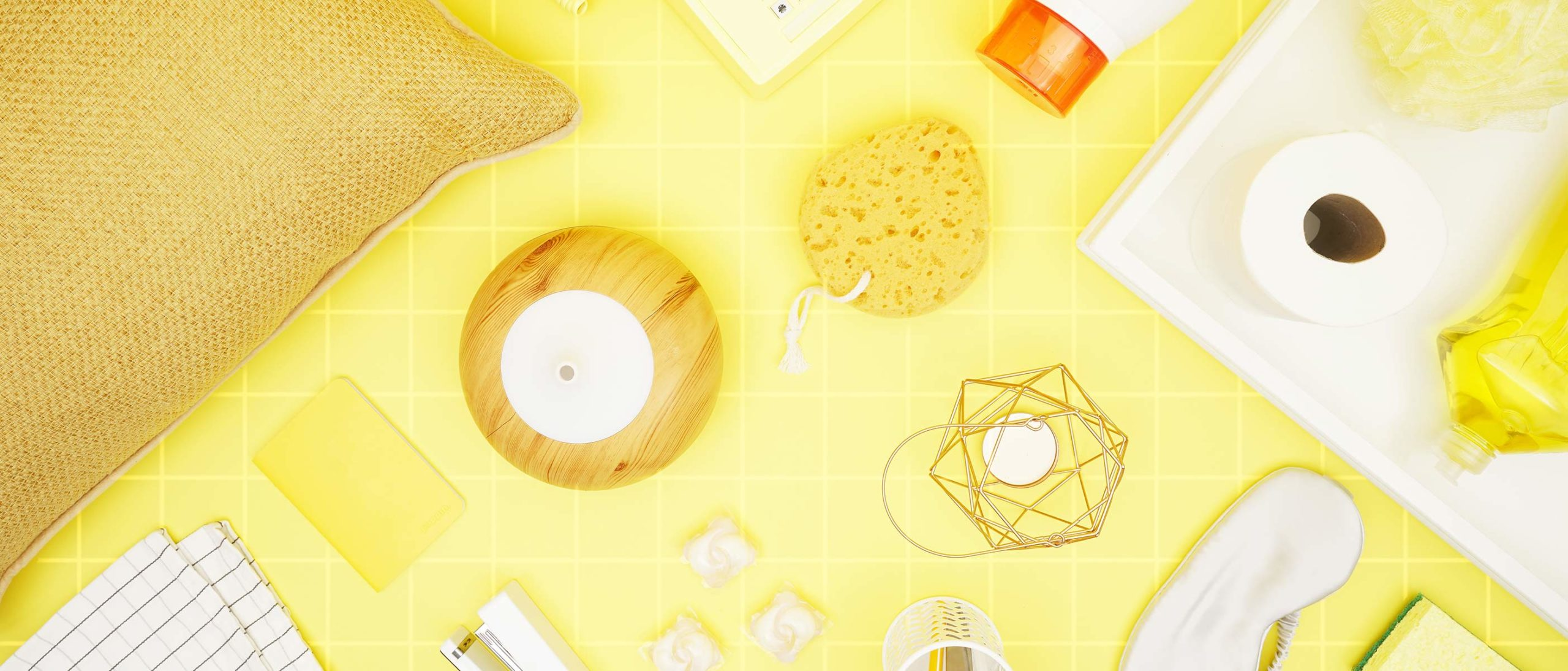 various dorm-related items laid out on a yellow backround: pillow, humidifier, toilet paper, laundry detergent, loofah, sleeping mask