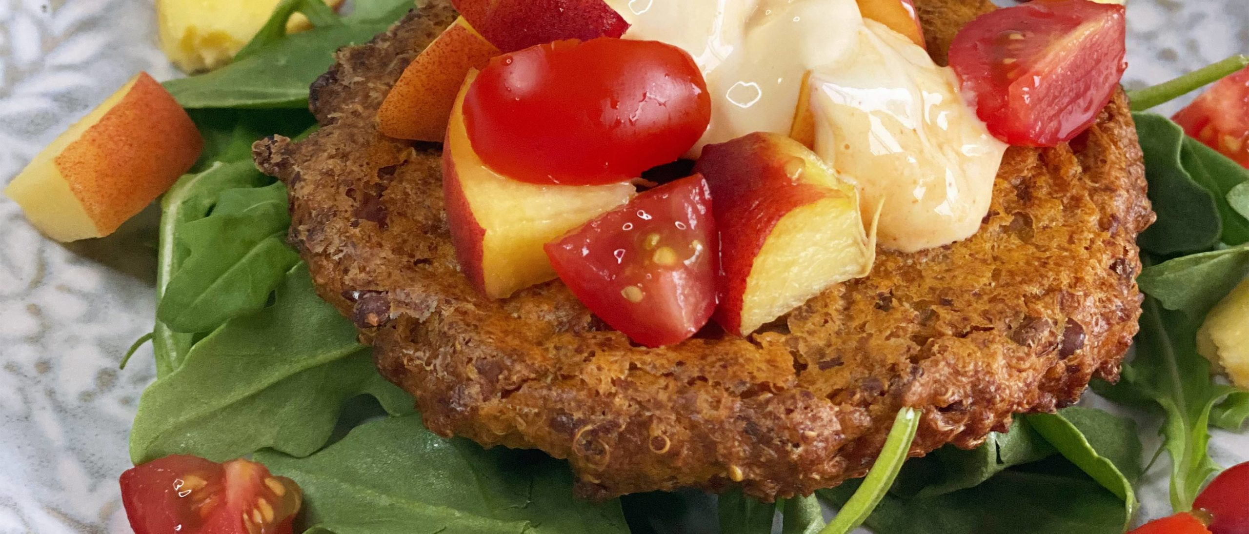 A Burget patty on a bed of lettuce and topped with peaches and cherry tomatoes
