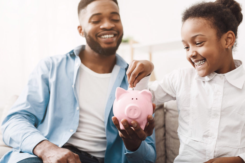 A father and daughter putting money in a piggy bank.