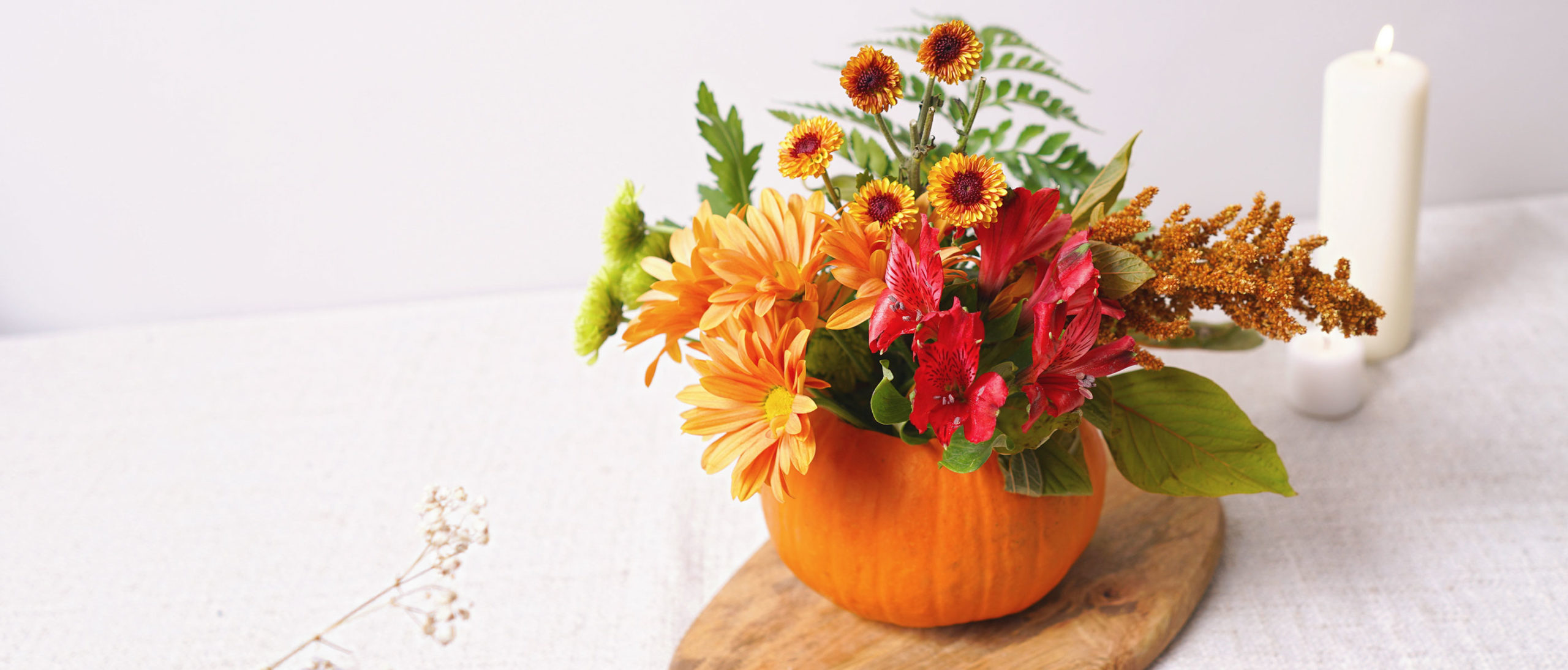 Header image of pumpkin vase with fall flowers